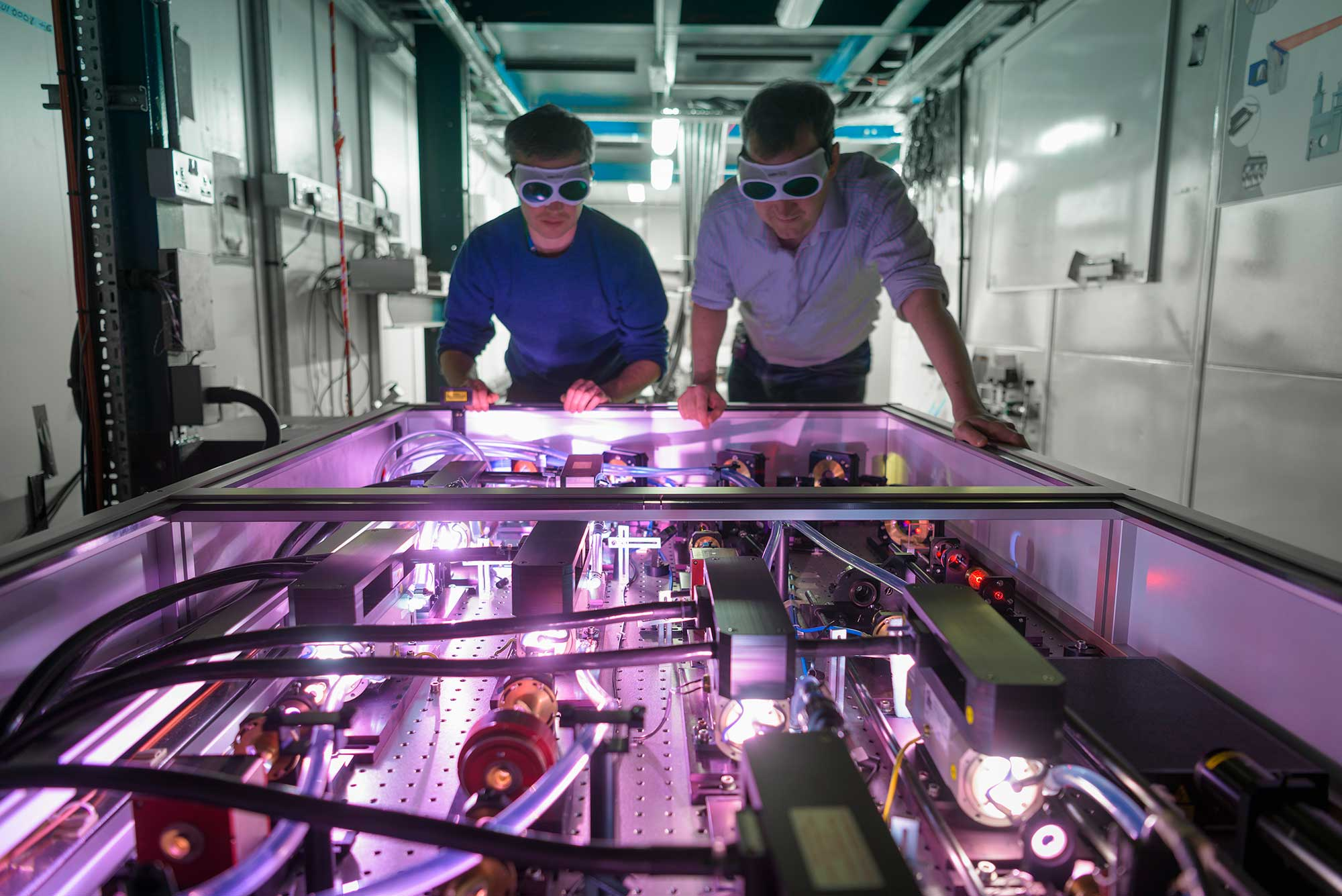Scientists inspecting laser system